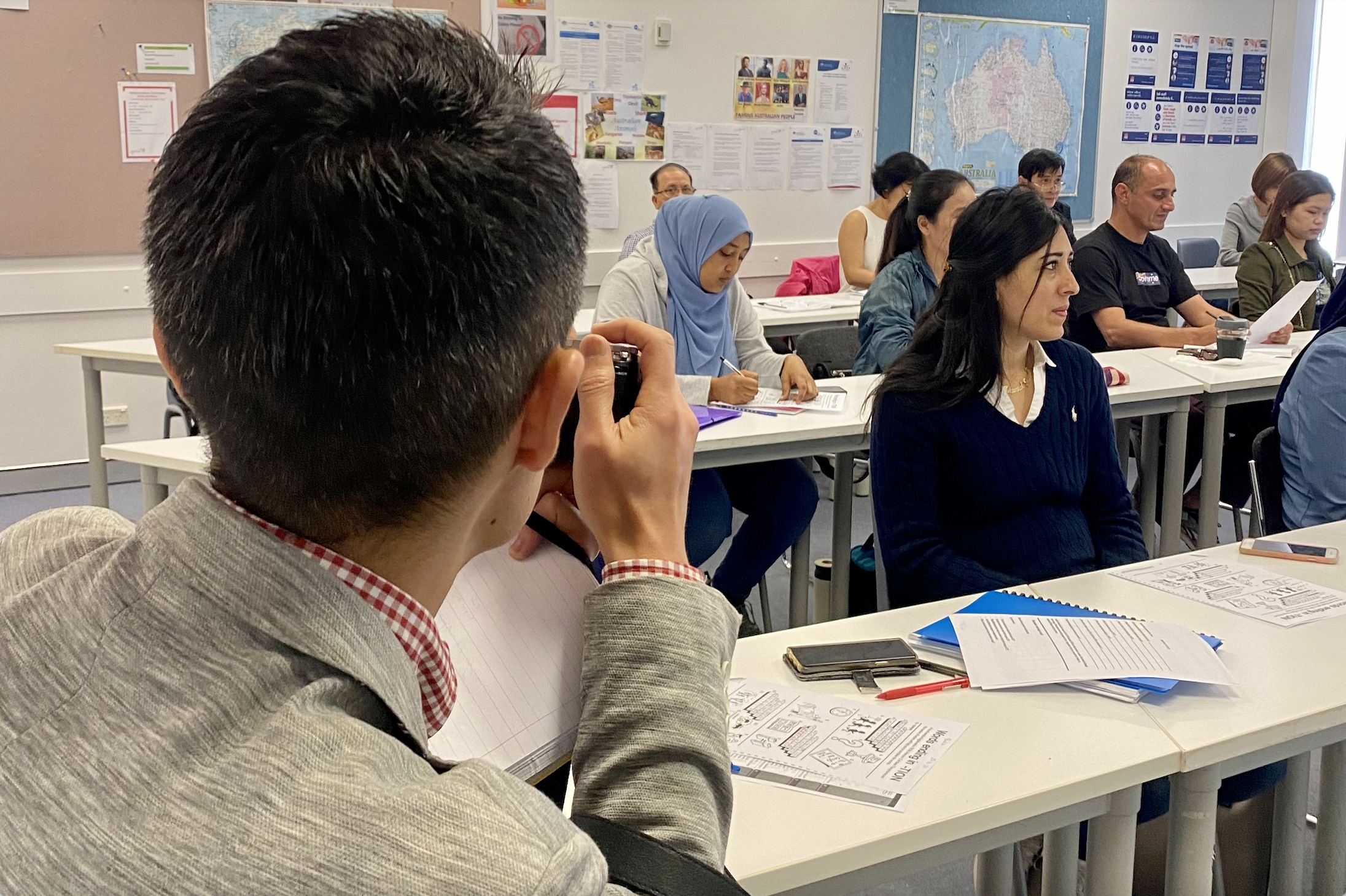 Adults learning in a classroom. Man taking a picture of them