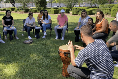 People sitting in a drum circle outside