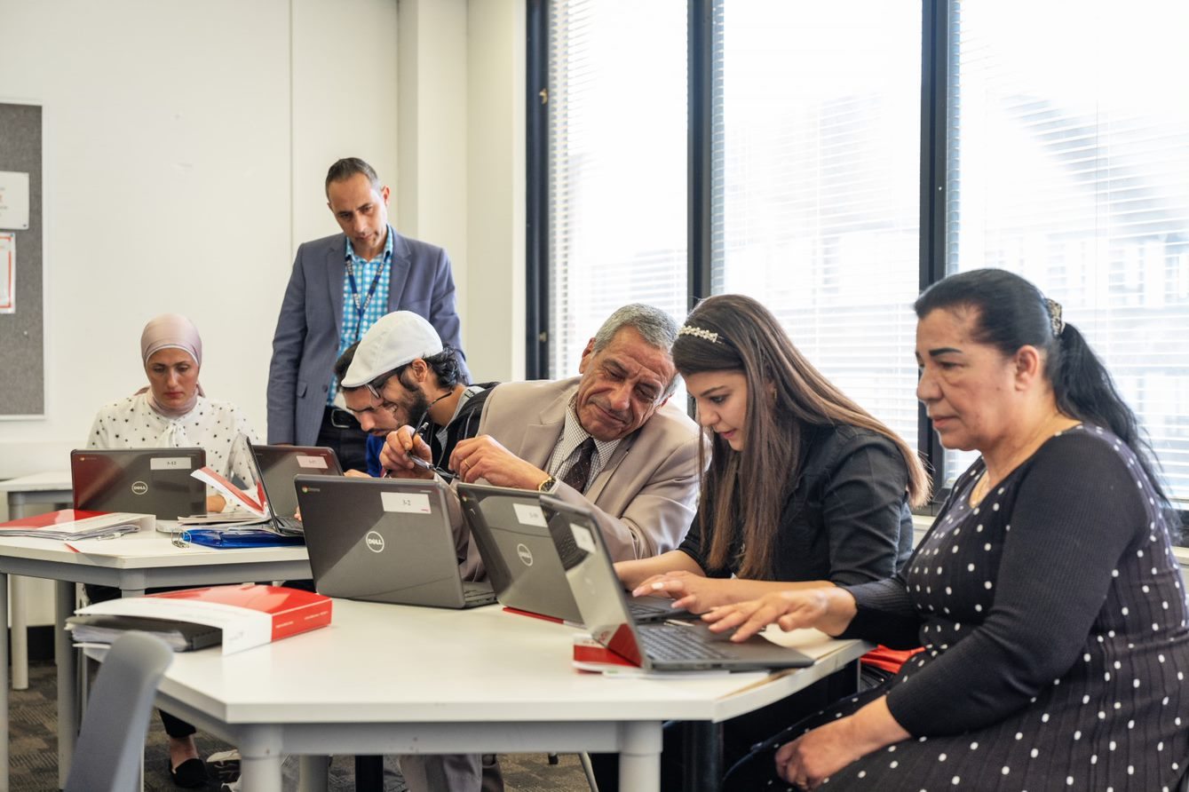 People from diverse backgrounds working on computers together.